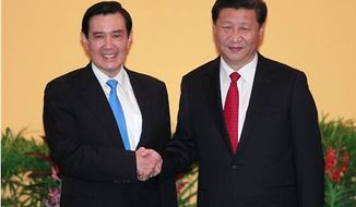 Taiwan's President Ma Ying-jeou, left, and China's President Xi Jinping shake hands at the Shangri-la Hotel on Saturday, Nov. 7, 2015, in Singapore. The two leaders shook hands at the start of a historic meeting, marking the first top level contact between the formerly bitter Cold War foes since they split amid civil war 66 years ago. (AP Photo/Chiang Ying-ying)