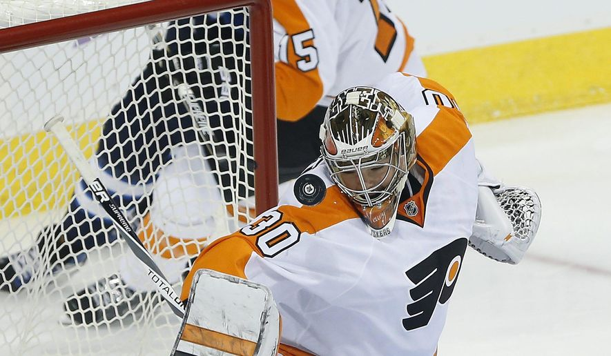 Philadelphia Flyers' goaltender Michal Neuvirth (30) keeps his eye on the puck after he makes the save on Winnipeg Jets' Mathieu Perreault and teammate Dustin Byfuglien (33) as Flyers' Michael Del Zotto (15) look on during first period NHL action, in Winnipeg, on Saturday, Nov. 7, 2015. (John Woods/The Canadian Press via AP)