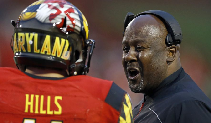 Maryland interim head coach Mike Locksley, right, speaks with quarterback Perry Hills on the sideline in the first half of an NCAA college football game against Wisconsin, Saturday, Nov. 7, 2015, in College Park, Md. Wisconsin won 31-24. (AP Photo/Patrick Semansky)