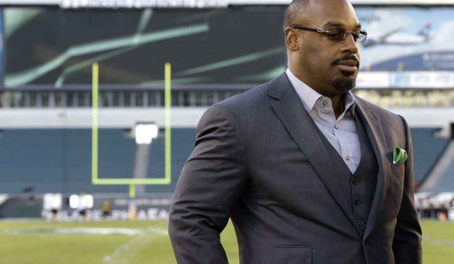 FILE - In this Sept. 19, 2013, file photo, former Philadelphia Eagles quarterback Donovan McNabb pauses during a television interview before an NFL football game against the Kansas City Chiefs, in Philadelphia. McNabb will serve 18 days in an Arizona jail after he pleaded guilty to a non-extreme DUI. McNabb was stopped by police in the Phoenix suburb of Gilbert on June 28, 2015, while driving impaired. (AP Photo/Julio Cortez, File)