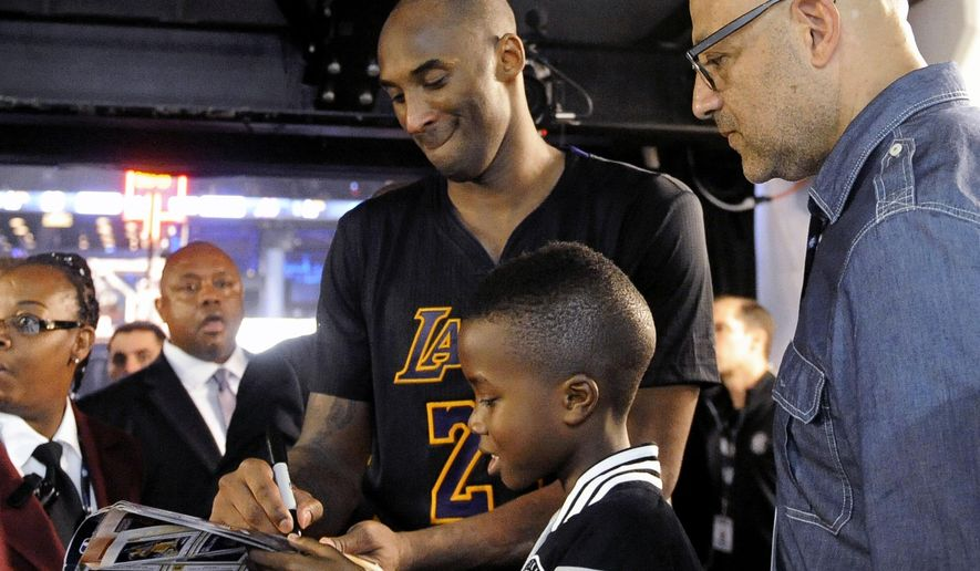 Los Angeles Lakers forward Kobe Bryant signs an autograph for a young fan as he walks off the court after the Lakers defeated the Brooklyn Nets 104-98 in an NBA basketball game Friday, Nov. 6, 2015, in New York. (AP Photo/Kathy Kmonicek)