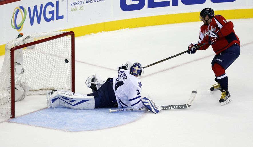 Washington Capitals left wing Alex Ovechkin (8), from Russia, scores the winning goal past Toronto Maple Leafs goalie James Reimer (34) in the shootout portion of an NHL hockey game, Saturday, Nov. 7, 2015, in Washington. The Capitals won 3-2 in overtime. (AP Photo/Alex Brandon)