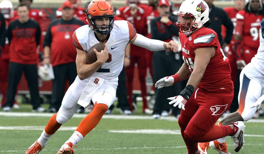 Syracuse quarterback Eric Dungey, left, attempts to scramble away from the defense of Louisville's Pio Vatuvei during the second half of an NCAA college football game Saturday, Nov. 7, 2015, in Louisville, Ky. Louisville won 41-17. (AP Photo/Timothy D. Easley)
