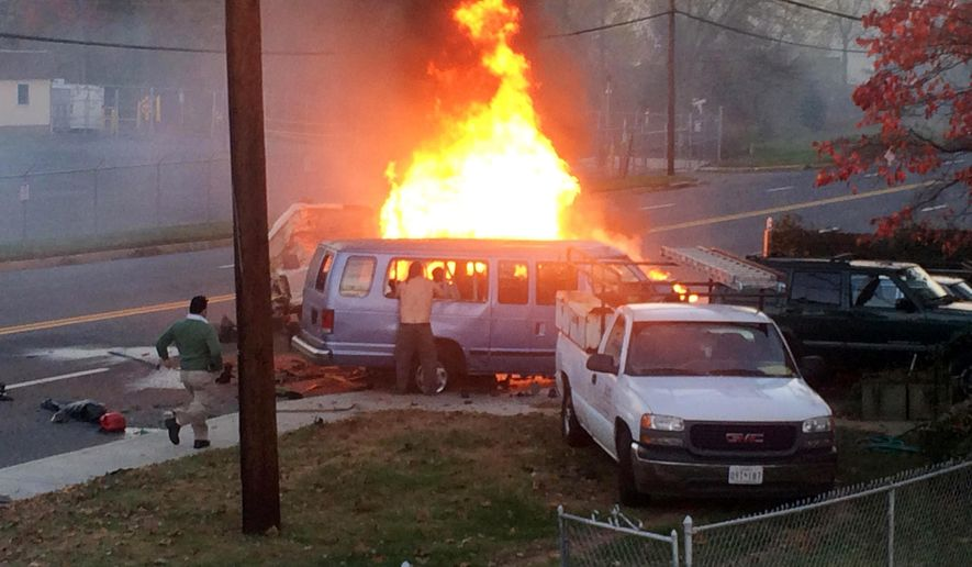 Flames rise from a vehicle following a fatal crash Sunday, Nov. 8, 2015, in Hyattsville, Md. The accident occurred late Sunday afternoon on a road in Hyattsville just northeast of Washington. (Steve Ramsey via AP) MANDATORY CREDIT