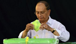 Myanmar's President Thein Sein casts his vote in Naypyitaw, Myanmar, Sunday, Nov. 8, 2015. Myanmar voted Sunday in historic elections that will test whether popular mandate can loosen the military's longstanding grip on power, even if opposition leader Aung San Suu Kyi's party secures a widely-expected victory. (AP Photo/Aung Shine Oo)