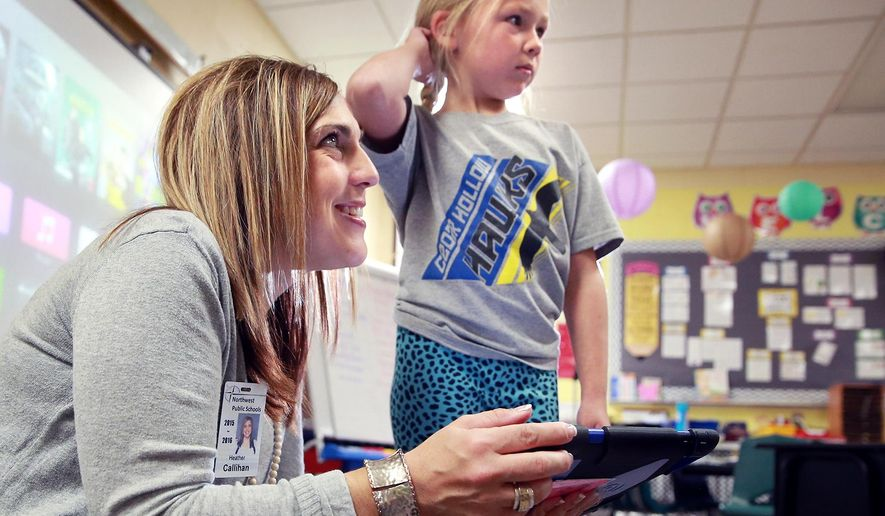 ADVANCE FOR USE SUNDAY, NOV. 8 - In this photo taken Oct. 30, 2015, Heather Callihan, Northwest Public Schools technology integration specialist, teaches good digital citizenship as she works with first-graders, including Addie Miller, right,, in Tami Wissing's classroom at Cedar Hollow School just west of Grand Island, Neb. (Barrett Stinson/The Independent via AP) MANDATORY CREDIT, TV OUT, RADIO OUT, MAGAZINES OUT.