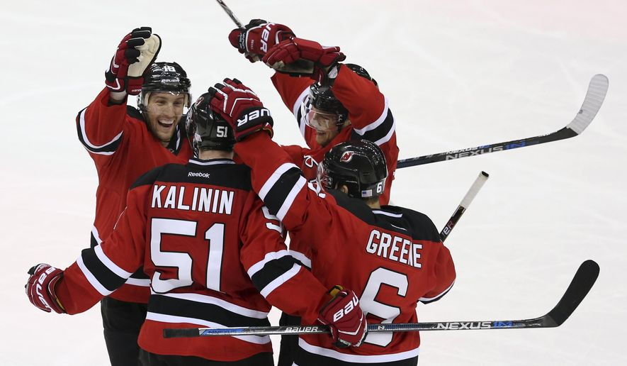 New Jersey Devils center Travis Zajac (19), center Adam Larsson (5), of Sweden, and defenseman Andy Greene (6) celebrate a goal by center Sergey Kalinin (51), of Russia, during the second period of an NHL hockey game against Vancouver Canucks, Sunday, Nov. 8, 2015, Newark, N.J. (AP Photo/Mel Evans)