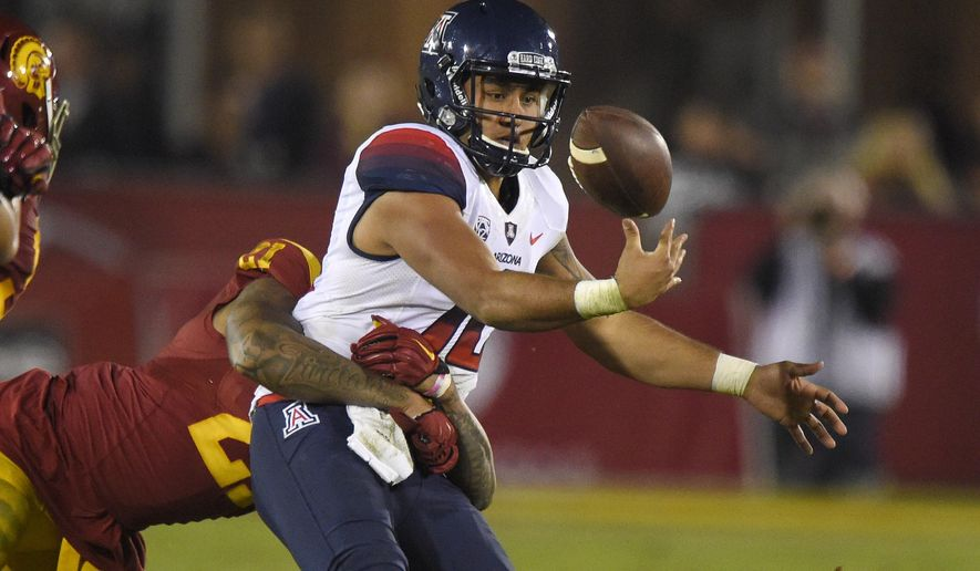 Arizona quarterback Anu Solomon, right, fumbles the ball as he is tackled by Southern California linebacker Su'a Cravens during the second half of an NCAA college football game, Sunday, Nov. 8, 2015, in Los Angeles. Southern California won 38-30. (AP Photo/Mark J. Terrill)