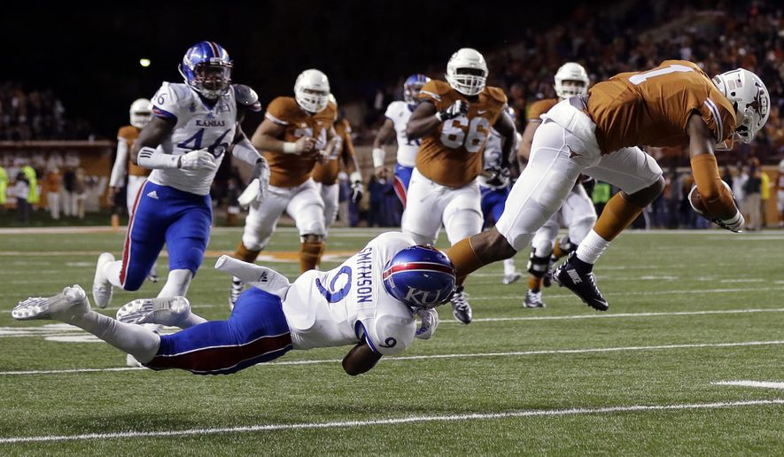 Texas wide receiver John Burt (1) is stopped by Kansas safety Fish Smithson (9) after a reception during the second half of an NCAA college football game, Saturday, Nov. 7, 2015, in Austin, Texas. (AP Photo/Eric Gay)