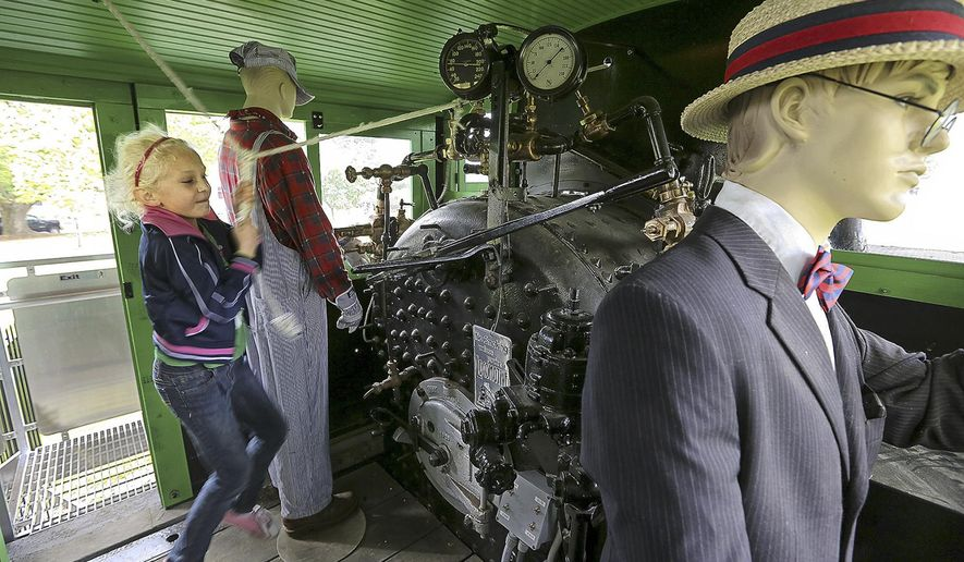 Jasmine Kruis of Kelso, Wash., put her all into ringing the bell on Shay No. 5 as the restored logging locomotive was open for public tours after the re-dedication ceremonies. (Bill Wagner/The Daily News via AP)