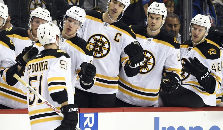 Boston Bruins Ryan Spooner (51) is congratulated by teammates after scoring a goal against the New York Islanders during the first period of an NHL hockey game on Sunday, Nov. 8, 2015, in New York. (AP Photo/Kathy Kmonicek)