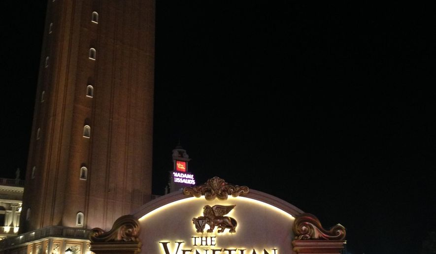 A police vehicle is parked next to the Venetian in Las Vegas, Saturday, Nov. 7, 2015. Las Vegas police say a man jumped off a pedestrian bridge at the Venetian resort after officers arrived to see the man hanging over the bridge armed with razor blades. (AP Photo/Kimberly Pierceall)