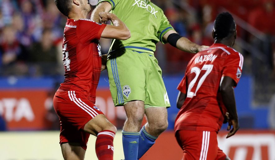 Seattle Sounders FC defender Chad Marshall, center, goes up for a header against FC Dallas defender Matt Hedges, left, during the first half of an MLS soccer western conference semifinal playoff match Sunday, Nov. 8, 2015, in Frisco, Texas. FC Dallas defender/midfielder Je-Vaughn Watson (27) is at right. (AP Photo/Brad Loper)