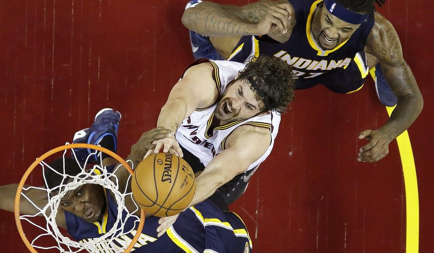 Cleveland Cavaliers forward Kevin Love, center, shots between Indiana Pacers center Ian Mahinmi (28) and center Jordan Hill (27) during the second half of an NBA basketball game Sunday, Nov. 8, 2015, in Cleveland. The Cavaliers won 101-97. (AP Photo/Ron Schwane)