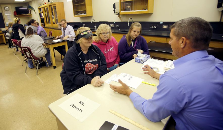 ADVANCE FOR SUNDAY, NOV. 8, 2015- In this photo taken on Thursday, Oct. 29, 2015, DeeAnn Carner, from left, Diane Conley, and eighth-grader Ashtan Carner, 13, take part in a parent-teacher conference with science teacher Chris Streets at Thomas Jefferson Middle School, in Dubuque, Iowa. (Mike Burley /Telegraph Herald via AP) MANDATORY CREDIT