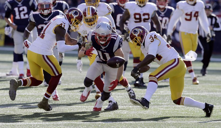 New England Patriots wide receiver Julian Edelman (11) fumbles between Washington Redskins defensive backs Will Blackmon (41) and Trenton Robinson (34) during the first half of an NFL football game, Sunday, Nov. 8, 2015, in Foxborough, Mass. Blackmon recovered the fumble. (AP Photo/Charles Krupa)