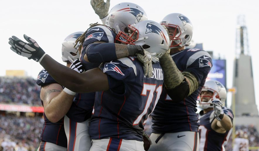 New England Patriots running back Brandon Bolden celebrates with guard Cameron Fleming (71) after scoring a touchdown in against the Washington Redskins during the second half of an NFL football game Sunday, Nov. 8, 2015, in Foxborough, Mass. (AP Photo/Steven Senne)