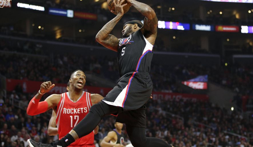 Los Angeles Clippers' Josh Smith, center, gets a rebound as Houston Rockets' Dwight Howard watches during the first half of an NBA basketball game, Saturday, Nov. 7, 2015, in Los Angeles. (AP Photo/Jae C. Hong)