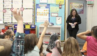 A student teacher in the second-grade classroom of teacher Susanne Diaz at Marcus Whitman Elementary School, goes over lessons with students, in Richland, Wash. (Ty Beaver/The Tri-City Herald via AP) ** FILE **