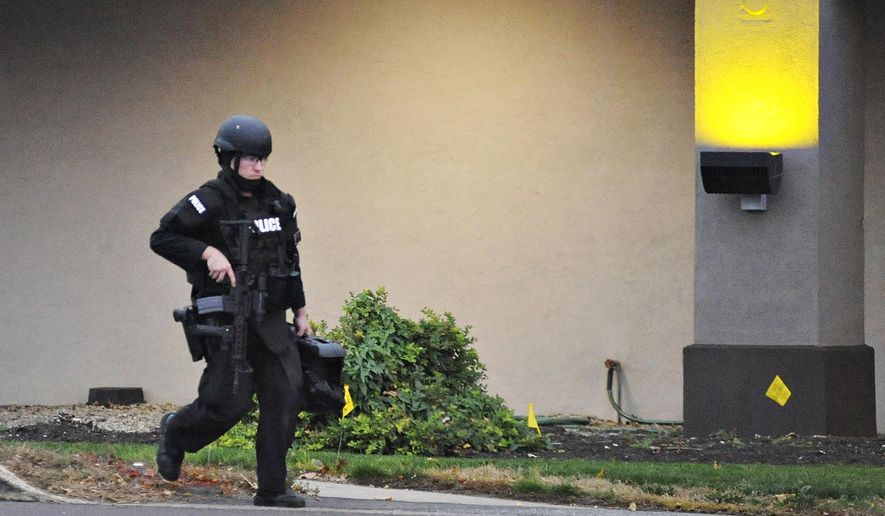 A police officer walks in front of Knights Inn after reports of a shooting in Bensalem Township near Trevose, Pa., Saturday, Nov. 7, 2015. Police seeking someone on a parole violation stumbled upon another man and a woman who were wanted in a double homicide in North Carolina, and that man is dead after a standoff at the motel, authorities said Saturday. (Rick Kintzel/The Intelligencer via AP) MANDATORY CREDIT