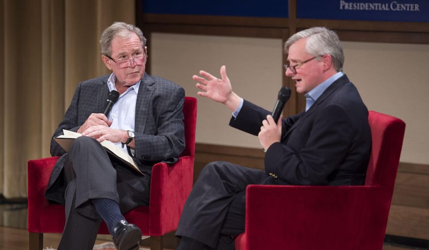 Former President George W. Bush, left, listens to Pulitzer Prize winning author Jon Meacham, right, talk about his biography of Bush's father, former President George H. W. Bush, Sunday, Nov. 8, 2015 at the George W. Bush Presidential Center in Dallas. (AP Photo/Jeffrey McWhorter)