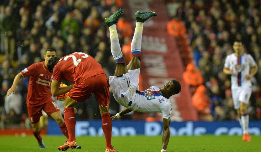 Crystal Palace's Wilfried Zaha, right, battles for the ball with Liverpool's Emre Can during the English Premier League soccer match at Anfield, Liverpool, England, Sunday Nov. 8, 2015. (Martin Rickett/PA via AP) UNITED KINGDOM OUT