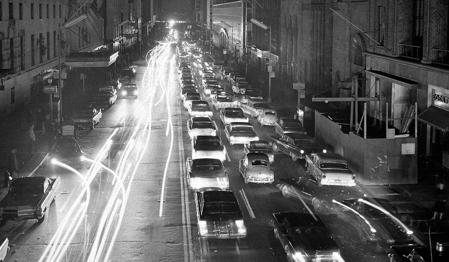 FILE - In this Nov. 9, 1965, file photo, cars move slowly on 42nd Street in New York, after a massive blackout in the northeastern United States. The time lapse photo looks east, between Park Avenue and Lexington Avenue. (AP Photo/Robert Goldberg, File)