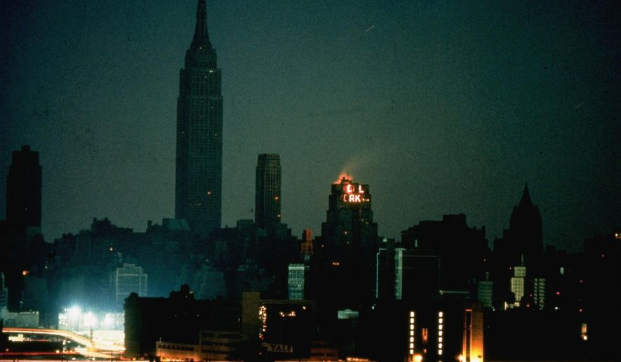 FILE - In this Nov. 9, 1965, file photo, New York City is seen in darkness from the Queens neighborhood of Long Island City during a power failure that left most of the northeastern United States and parts of Canada without power for hours. The buildings with lights had emergency power generators. (AP Photo/File)
