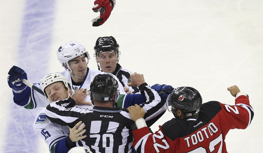 New Jersey Devils right wing Jordin Tootoo (22) fights with Vancouver Canucks right wingers Alexandre Burrows (14) and Derek Dorsett (15) during the second period of an NHL hockey game, Sunday, Nov. 8, 2015, Newark, N.J. The Devils won in overtime 4-3. (AP Photo/Mel Evans)