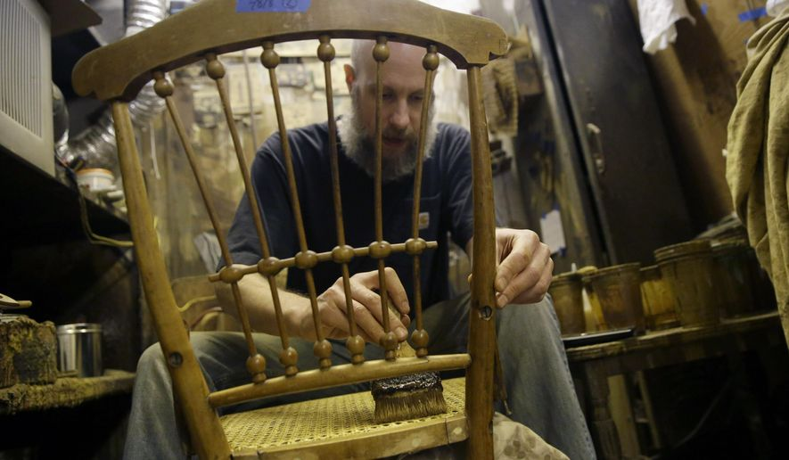 In this Thursday, Nov. 5, 2015, photo, Sean Bausert stains a chair at the Veterans Caning & Repair shop in New York. In a dusty, cluttered shop that seems oddly out of place in modern New York, a group of artisans is among the last still practicing a dying trade: chair caning. The painstaking art of weaving furniture details in a honeycomb pattern is still in demand, mostly for repair work, but the shop that's been around since the 1860s is under threat from a new wave of high-rise development on Manhattan's west side. (AP Photo/Mary Altaffer)