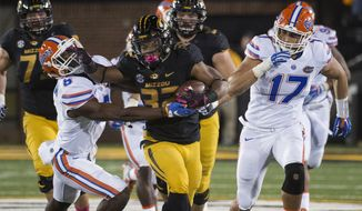 In this Oct. 10, 2015, file photo, Missouri running back Russell Hansbrough, center, fights his way past Florida's Nick Washington, left, and Jordan Sherit, right, during an NCAA college football game in Columbia, Mo. Some Missouri football players announced Saturday night, Nov. 7, 2015, on Twitter that they will not participate in team activities until the university president, Tim Wolfe, is removed from office. The statement from the athletes of color was tweeted out Saturday by several members of the football team, including Hansbrough. (AP Photo/L.G. Patterson. File)