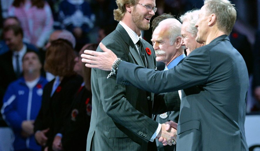 Hall-of-Famer Chris Pronger, left, shakes hands with Hockey Hall of Fame officials prior to NHL hockey game action between the Toronto Maple Leafs and the Detroit Red Wings in Toronto on Friday, Nov. 6, 2015. (Nathan Denette/The Canadian Press via AP) MANDATORY CREDIT