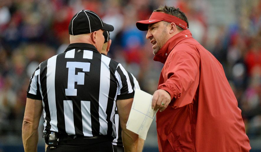 Arkansas head coach Bret Bielema, right, talks with referees during the second quarter of an NCAA college football game against Mississippi in Oxford, Miss., Saturday, Nov. 7, 2015. (AP Photo/Thomas Graning)