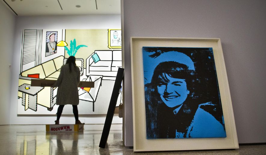 """Andy Warhol's """"Blue Jackie,"""" right, and Roy Lichtenstein's """"Interior with Yves Klein Sculpture,"""" left, are among master works being installed at Christie's for the upcoming New York evening art auctions of impressionist, modern and post-war art, during a press preview, Friday Oct. 30, 2015, in New York. (AP Photo/Bebeto Matthews)"""