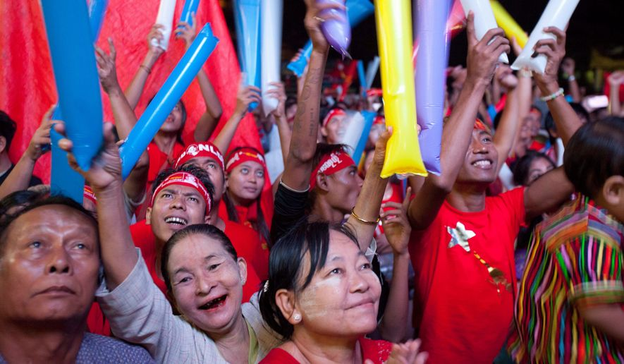 Supporters of Myanmar opposition leader Aung San Suu Kyi's National League for Democracy party cheer as they watch the results of the general election outside the party's headquarters Monday. (Associated Press)