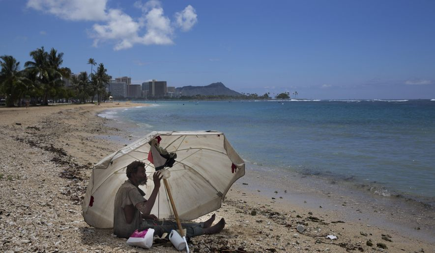 In this Thursday, Aug. 27, 2015 photo, a homeless man drinks water while sitting on the beach at Ala Moana Beach Park located near Waikiki in Honolulu. Homelessness in Hawaii has grown steadily in recent years, leaving the state with the nation's highest rate of homeless people per capita. (AP Photo/Jae C. Hong)
