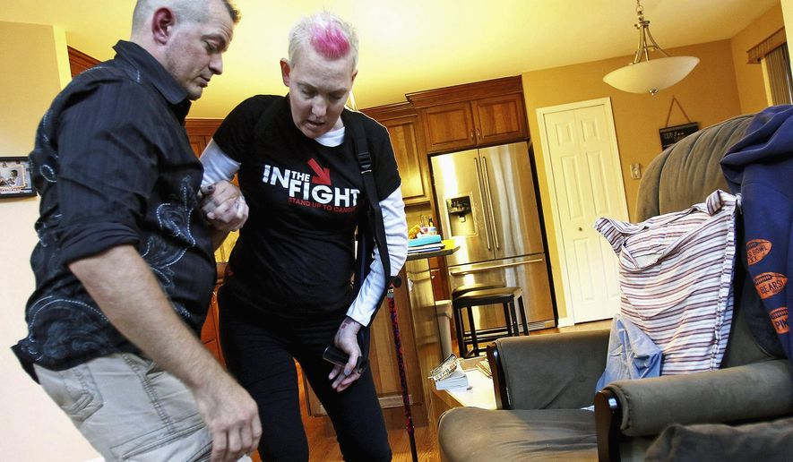 In this Oct. 22, 2015 photo, Meghan Korbecki, who is battling brain cancer for the third time, has help getting into a chair from husband, Bill, before dinner at their home in Crystal Lake, Ill. (Matthew Apgar/Northwest Herald via AP)  CHICAGO TRIBUNE OUT, MANDATORY CREDIT
