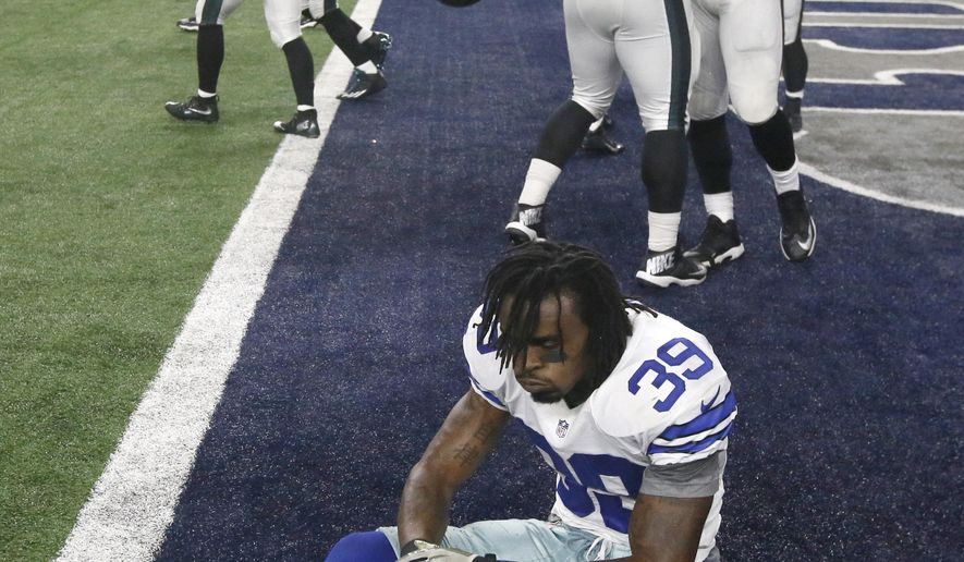 Dallas Cowboys' Brandon Carr (39) sits on the field as Philadelphia Eagles' Josh Andrews (68) celebrates with teammates after the Eagles 33-27 in in overtime of an NFL football game, Sunday, Nov. 8, 2015, in Arlington, Texas. (AP Photo/Michael Ainsworth)