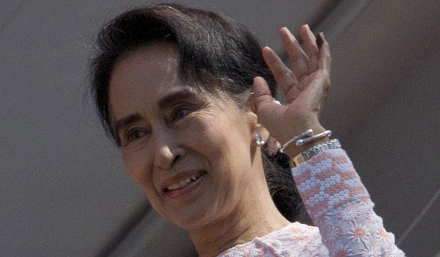Myanmar's opposition National League for Democracy party leader Aung San Suu Kyi, with ink still imprinted on the little finger of her left hand after voting yesterday, waves after delivering a speech from a balcony of the NLD headquarters in Yangon, Myanmar, Monday, Nov. 9, 2015. (AP Photo/Gemunu Amarasinghe) ** FILE **