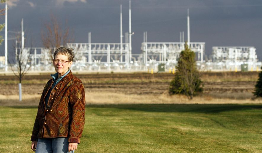 In a Nov. 5, 2015 photo, Kathy Blanchard stands on her property, where the Pleasant Valley Wind Farm Substation is clearly visible, outside Sargeant, Minn. In addition to the noise of the turbines, Kathy and Dan Blanchard believe the windmills are spoiling their view and disrupting their television signals.  (Elizabeth Nida Obert/Rochester Post-Bulletin via AP)
