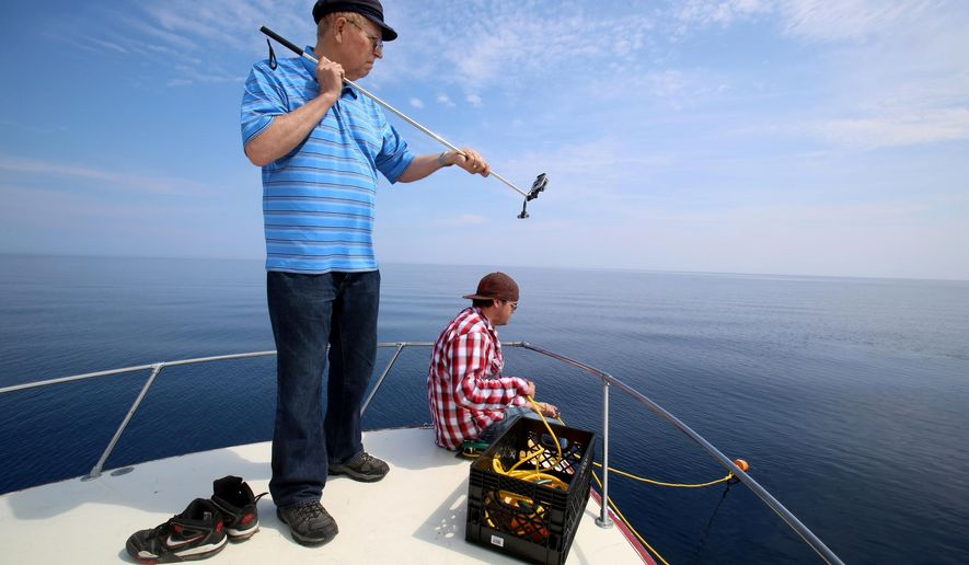 In a Saturday, July 11, 2015 photo, shipwreck hunter David Trotter, left, uses his GoPro on a selfie stick to shoot video as diver Jared Daniel looks on at the bow of Trotter's dive boat on Lake Huron. Trotter of Canton, Mich., says he and his crew believe they've found the wreck of the Hydrus, a ship that went down in Lake Huron during a major 1913 storm. Trotter tells the Detroit Free Press the Hydrus was found in July roughly 32 miles from land. after what was a 30 year effort for Trotter.  (Eric Seals/Detroit Free Press via AP)  DETROIT NEWS OUT; TV OUT; MAGS OUT; NO SALES; MANDATORY CREDIT DETROIT FREE PRESS
