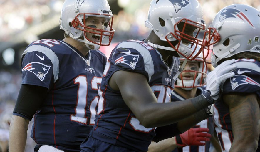 New England Patriots quarterback Tom Brady (12) and defensive end Chandler Jones, center, congratulate running back Brandon Bolden, right, after his touchdown against the Washington Redskins during the second half of an NFL football game Sunday, Nov. 8, 2015, in Foxborough, Mass. (AP Photo/Steven Senne)