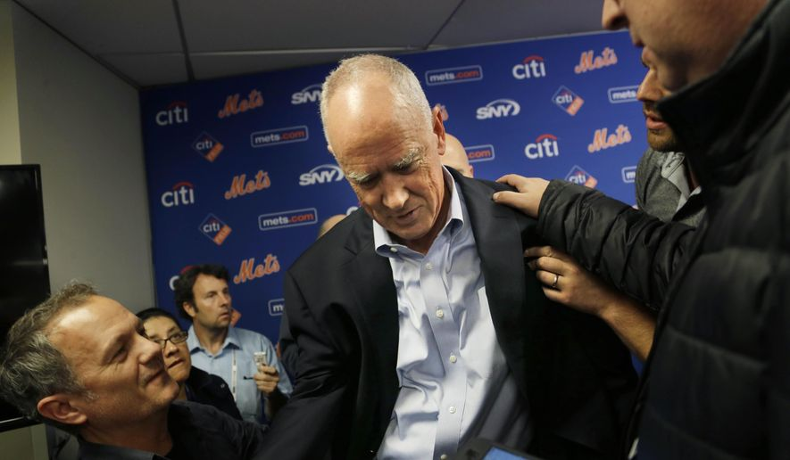 FILE - In this Nov. 4, 2015, file photo, New York Mets general manager Sandy Alderson is assisted to his feet by reporters after collapsing during a news conference in New York. Alderson will miss the annual GM meetings in Boca Raton, Fla., to undergo an unspecified medical procedure, a week after fainting during a news conference at Citi Field. Mets assistant general manager John Ricco made the announcement Monday, Nov. 9, 2015,  at the start of the four-day session. (AP Photo/Seth Wenig, File)