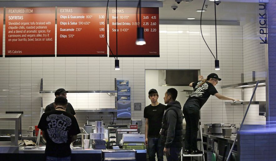 Workers clean inside a still-closed Chipotle restaurant Monday, Nov. 9, 2015, in Seattle. Health officials in Washington and Oregon have said that more than three dozen people have gotten sick with E. coli in an outbreak linked to Chipotle restaurants in the two states. More than 40 Chipotle restaurants remain closed in Washington state and the Portland area while authorities search for the cause. (AP Photo/Elaine Thompson)