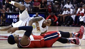 Atlanta Hawks guard Jeff Teague, top, and Washington Wizards guard Bradley Beal collide while chasing after the ball during the second half of an NBA basketball game on Saturday, Nov. 7, 2015, in Atlanta. Atlanta won 114-99. (AP Photo/Jon Barash)