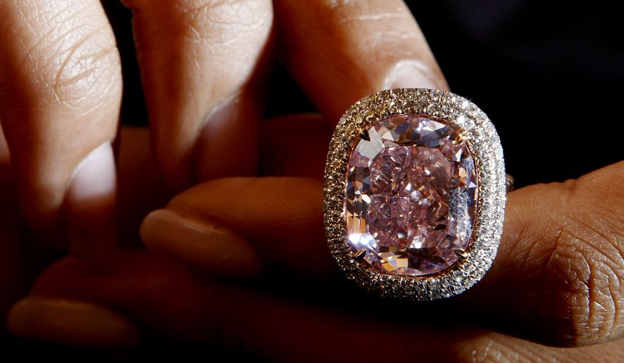 A Christie's employee presents a cushion-shaped fancy Vivid Pink diamond of 16.08 carats, during a preview at the Christie's auction house in Geneva, Switzerland, Friday, Oct. 30, 2015. The vivid diamond is estimated between $23 million to $28 million and will be sold during the Christie's auction Nov. 10 in Geneva. (Salvatore Di Nolfi/Keystone via AP, file)