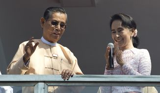 Leader of Myanmar's National League for Democracy party, Aung San Suu Kyi, delivers a speech with party patron Tin Oo from a balcony of her party's headquarters in Yangon, Myanmar, Monday, Nov. 9, 2015. Suu Kyi on Monday hinted that her party will win the country's historic elections, and urged supporters not to provoke their losing rivals. (AP Photo/Mark Baker)