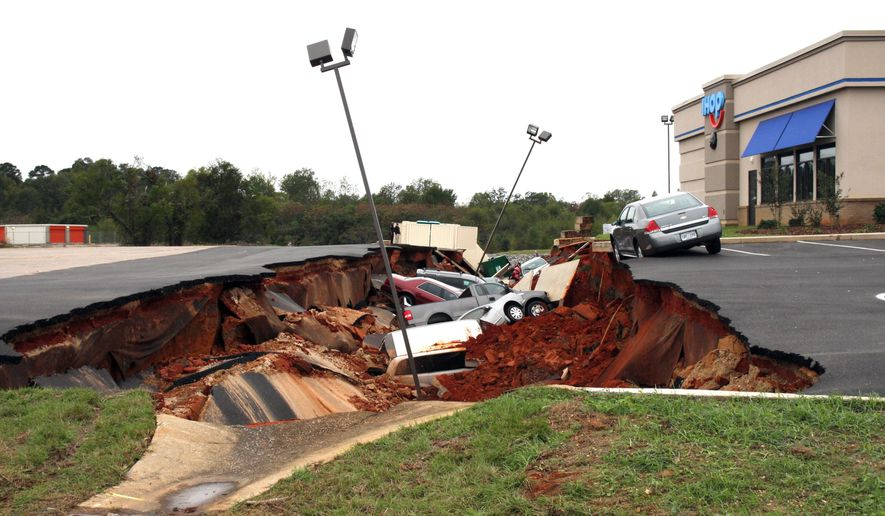 This photo shows vehicles after a cave-in of a restaurant parking lot in Meridian, Miss., Sunday, Nov. 8, 2015. Experts are to begin work Monday seeking to determine the cause of the Saturday collapse, authorities said. (Michael Stewart/The Meridian Star via AP) MANDATORY CREDIT