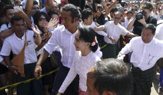 Myanmar opposition leader Aung San Suu Kyi is welcomed by supporters upon arrival at the headquarters of her National League for Democracy party. (AP Photo/Khin Maung Win)