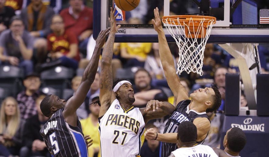Indiana Pacers center Jordan Hill (27) shoots between Orlando Magic guard Victor Oladipo (5) and forward Evan Fournier (10) during the first half of an NBA basketball game in Indianapolis, Monday, Nov. 9, 2015. (AP Photo/Michael Conroy)